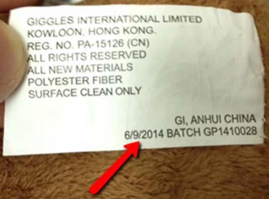 Manufacture date and batch code are printed on a white fabric label attached near the base of the tail.